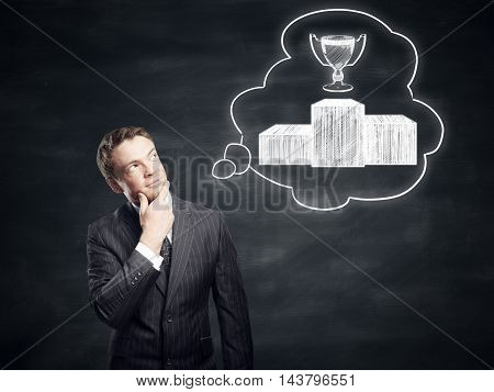Attractive businessman thinking about leadership on blackboard background