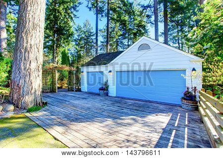 Separate Garage With Blue Door And Wooden Driveway.