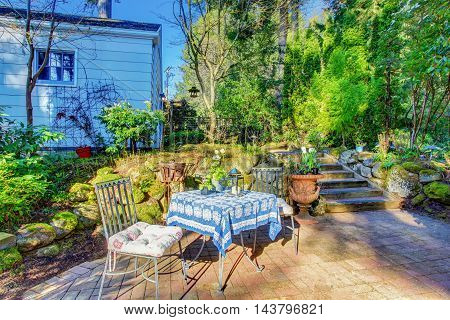 Backyard Patio Area With Table Set And Nice Landscaping Desing.