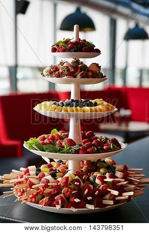 colorful fruit and berries pyramid on banquet