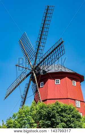 Closeup of large red windmill with very large arms.