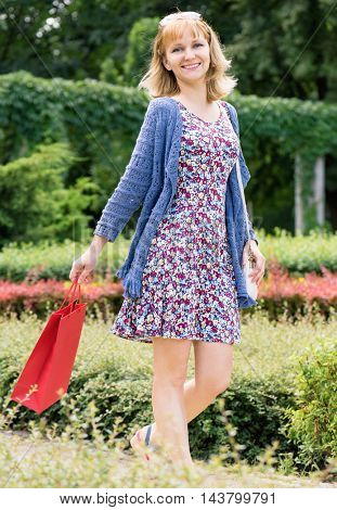 Beautiful young smiling girl with red shopping bag. Attractive happy caucasian young woman shopper dreamily smiling posing outdoors at park.