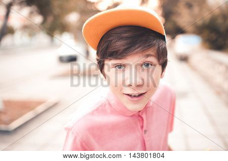 Stylish teen boy wearing cap and pink shirt outdoors. Having fun over city background. Looking at camera. Summer portrait of teenager closeup.