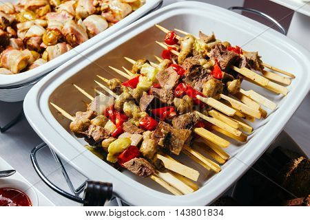 Meat, beef tongue, champinon on skewers grilled over charcoal. Lined in a beautiful white dish.