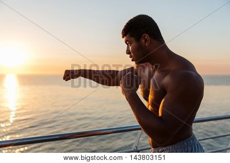 Silhouette of african american young man athlete practicing shadow boxing at sunrise