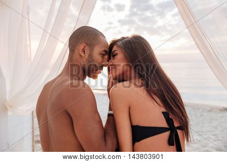 Sensual beautiful young couple kissing on the beach