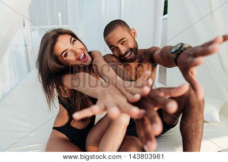 Lovely multircial couple in love having fun on the beach bed