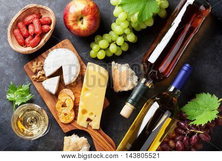 White wine, grape, bread and cheese on stone table. Top view