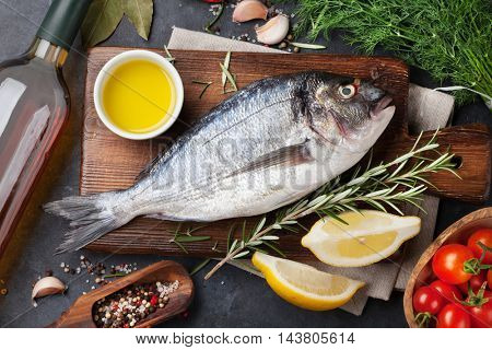 Raw fish cooking and ingredients. White wine, dorado, lemon, herbs and spices. Top view on stone table