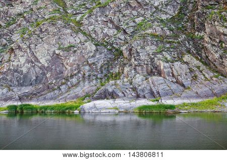 High rocks with lichen, scenic view from river