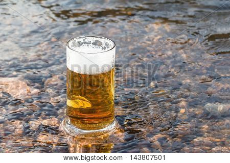 Mug fresh beer sparkles on the stone in the river