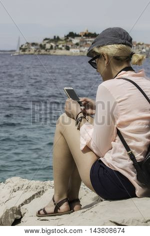 Woman in cap and with backpack is seating near of the sea and watching something in her phone