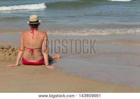 Woman In Red Bikini Resting On The Beach In Straw Hat