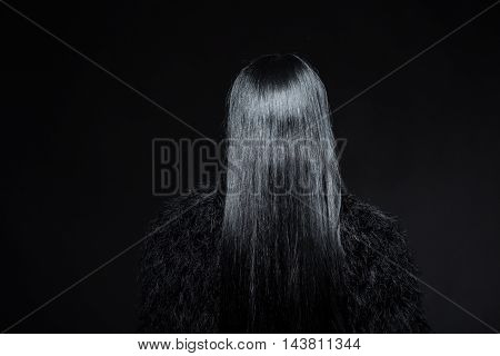 Closeup picture of brunette model woman demonstrating her gorgeous hair in studio. Beautiful lady showing black hair isolated on black background.