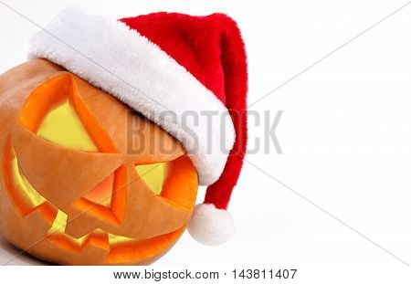 Spooky halloween pumpkin Jack O Lantern shiny inside wearing christmas hat on white background