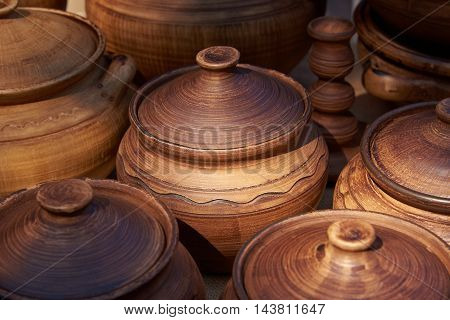 Ceramic pots with lids of clay handmade with natural sunlight. The image is focused on the central pot