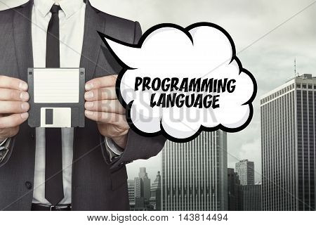 Programming language text on speech bubble with businessman holding diskette