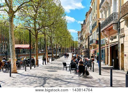 Perpignan France - April 8, 2016: People sitting in a sidewalk cafe on a promenade along the city canal of Perpignan. Pyrenees-Orientales France