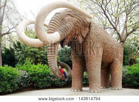 Little girl lying on an elephant's proboscis. Elephant statue in the Parc de la Ciutadella in Barcelona Spain