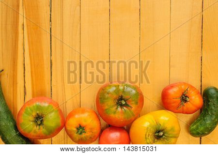 Heirloom tomatoes and cucumber on rustic background