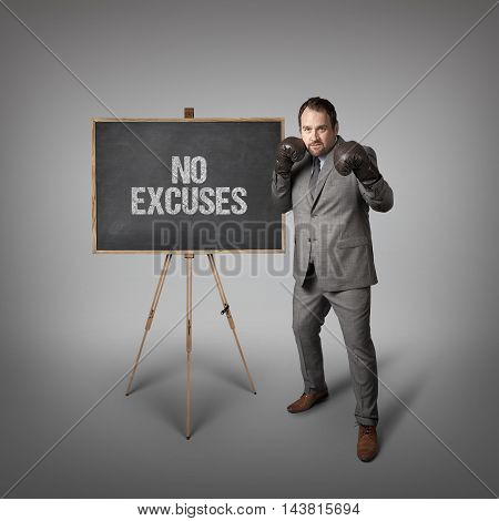 No excuses text on  blackboard with businessman wearing boxing gloves