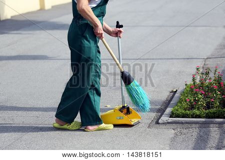 the a service janitor sweeping broom street