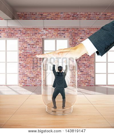 Employee miniature trapped inside transparent glass jar by employer's hand. Red brick interior background