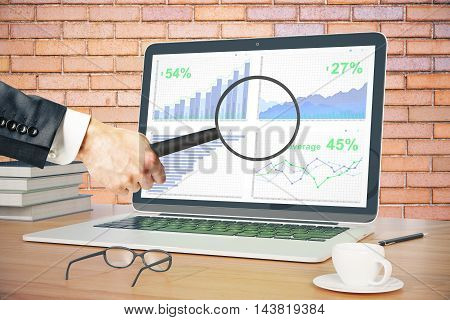Businessman holding magnifier over laptop screen with business graph on wooden desktop with coffee cup glasses pen and book. Red brick wall background. 3D Rendering