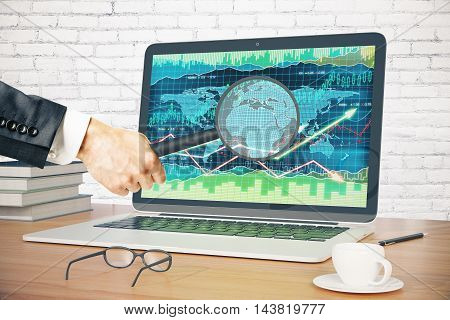 Businessman holding magnifier over laptop screen with forex graph on wooden desktop with coffee cup glasses pen and book. White brick wall background. 3D Rendering