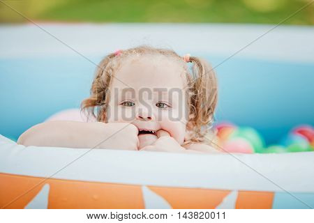 The Two-year old little baby girl playing with toys in inflatable pool in the summer sunny day