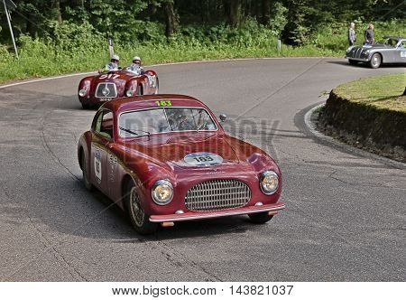 PASSO DELLA FUTA (FI) ITALY - MAY 21: driver and co-driver on a vintage sportscar Cisitalia 202 SC Berlinetta Pininfarina (1949) in classic car race Mille Miglia on May 21, 2016 in Passo della Futa (FI) Italy