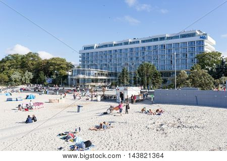 KOLOBRZEG - AUGUST 15: Tourists enjoy the sunny weather and relaxing on the Baltic sea beach on 15 August 2016 in Kolobrzeg, Poland.