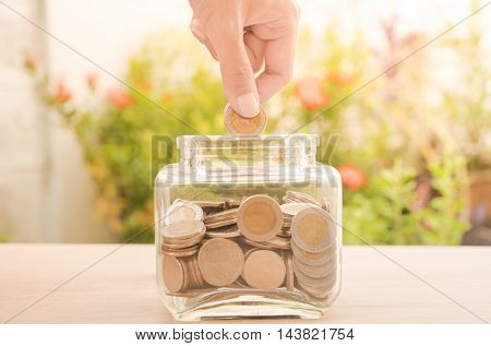 business hand holding money gold coin with business investment saving finance and banking concept.