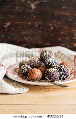 Assorted dark chocolate truffles with cocoa powder, homemade biscuits, coconut and chopped hazelnuts on a dessert plate, selective focus