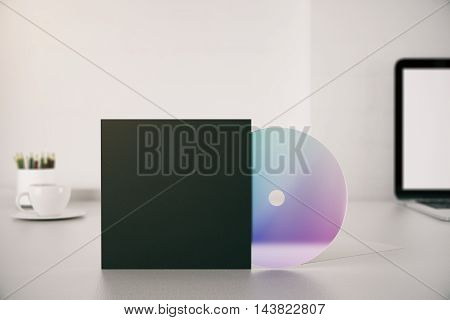 Closeup of empty black CD cover on desktop with laptop coffee cup and pencils. Mock up 3D Rendering