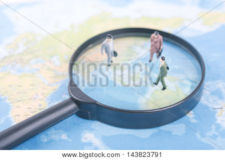 Miniature business people on magnifier and world map. business international travel concept