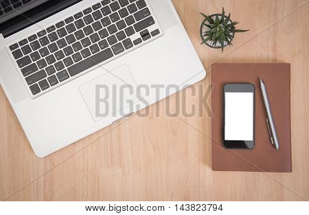 Business's desk of office supplies and gadgets computer telephone pen book cactus on empty wooden table background. Top View from above.