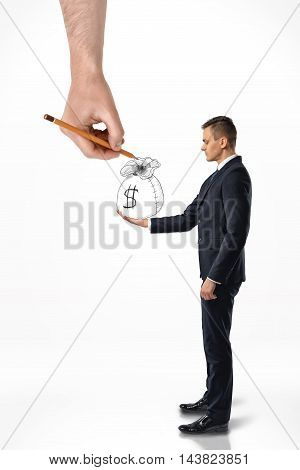 Side view of a businessman holding a hand-drawn bag of money with a big hand that draws it isolated on white background. Investment and profit. Business staff. Office clothes.
