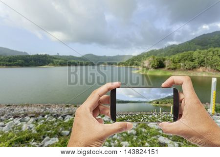 Hands holding phone and taking picture of Dam view with bad weather.