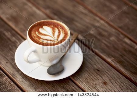 Cup of cappuccino with latte art on wooden table.