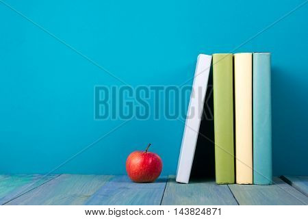 Row of books, grungy blue background, free copy space Vintage old hardback books on wooden shelf on the deck table, no labels, blank spine. Back to school. Education background