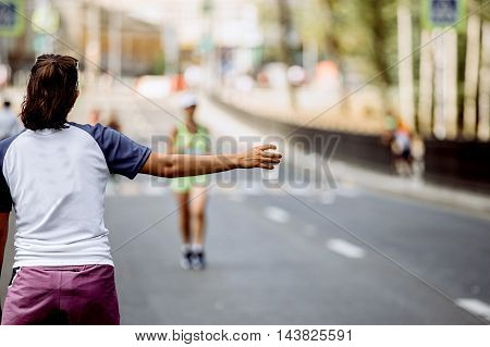 girl in hand a cup of at water point of marathon in background runner