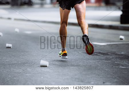male athlete running on asphalt of empty cups from water