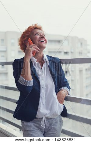 Mature woman talking on a smartphone on the balcony