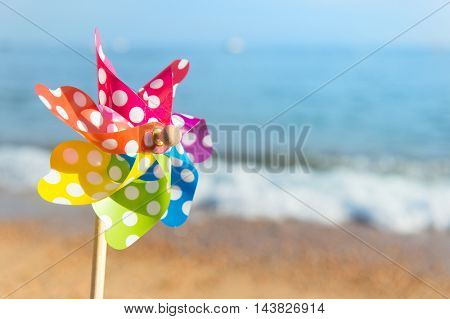 Colorful toy wind turbine at the beach