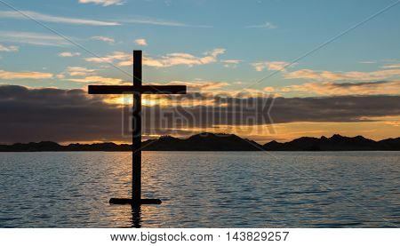 Black cross of salvation on a lake of water at sunset.