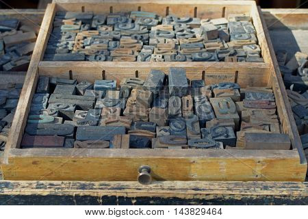 Box of antique wooden letters printing blocks letterpress type set. Abstract typography background.