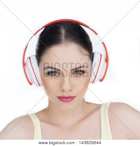 Closeup of a beautiful young brunette woman listening to music over white background