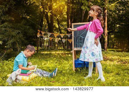 little girl explains at the blackboard math boy