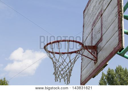 Basketball board with a net. Old wooden planks. Painted. Located on a background of blue sky with clouds. Sport games in the yard. Side view.